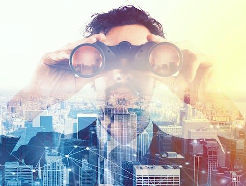 Un hombre de gtraje y barba mira con prismáticos sobre una ciudad moderna.