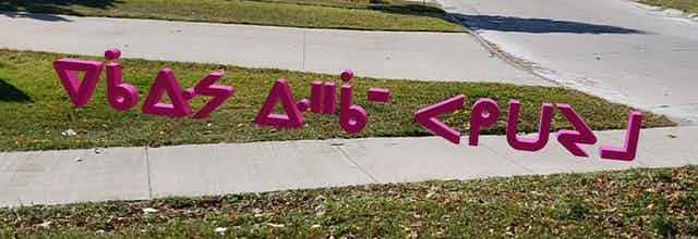 Cree language lettering floating over grass and pavement.