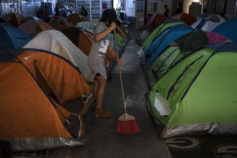 A woman sweeps the concrete floor amid rows of tents