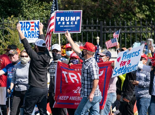 A lone Biden supporter holds a sign as as supporters of Donald Trump rally outside of Walter Reed Medical Center.