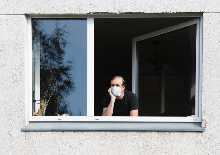 A man wearing a mask looks out the open window of his home.