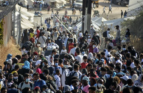 A large crowd of refugees, mostly wearing face masks.