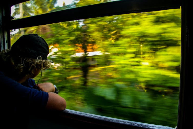 Man looking out of train window as scenery speeding by