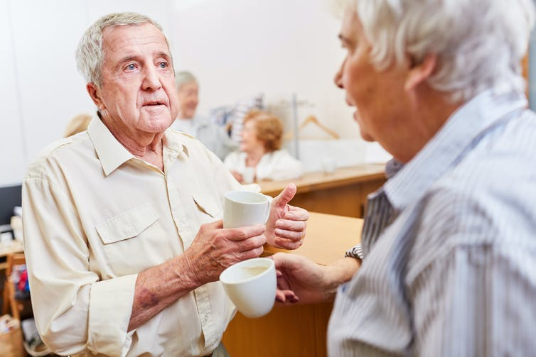 Two elderly men talking over a cup of coffee in an aged-care setting.
