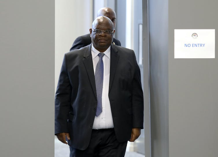 Deputy Chiec Justice Zondo wearing a black suit, blue tie and specs enters the the State capture commisssion venue