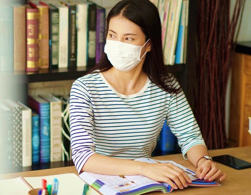Woman in library wearing mask