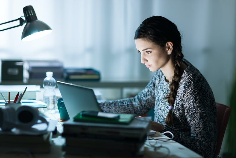 Woman studying with books and laptop