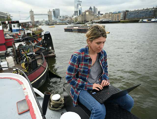 A woman sits with a laptop on her house barge on the Thames river.