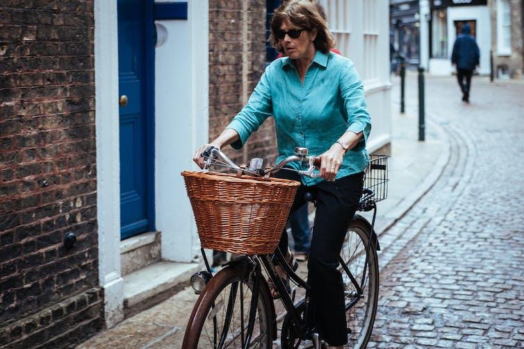 Una mujer pasa por una casa en su bicicleta con una canasta de mimbre al frente.