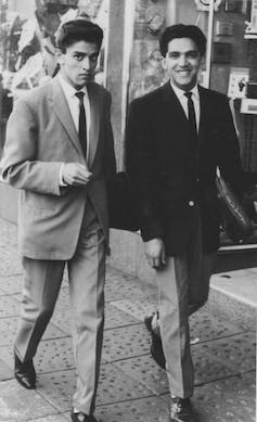 Two men walk along a pavement, both dapper in suits, the one looking at the camera questioningly and the other smiling at it broadly.