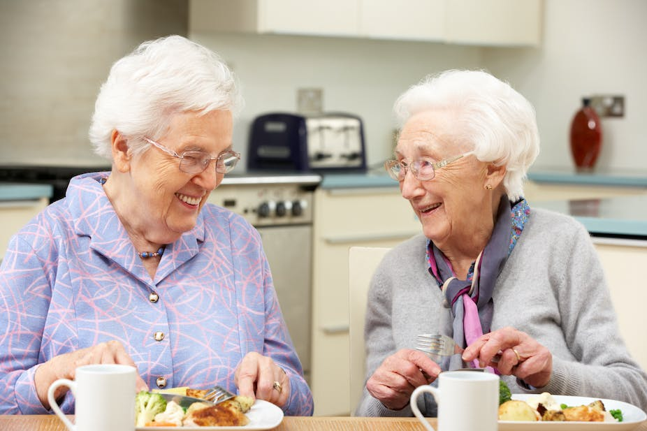 Two older women eat lunch together.
