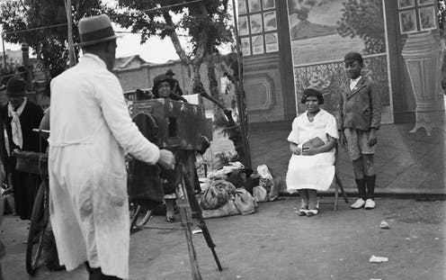A man in a hat and coat photographs a woman and boy against a backdrop of a smart home and a volcano erupting out to see. Rubbish and litter can be seen on the street, where a woman looks on.