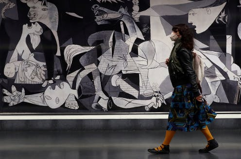 A woman wearing a mask walks past Picasso's painting Guernica