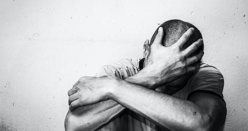 Hombre abatido se sujeta la cabeza con la palma abierta.