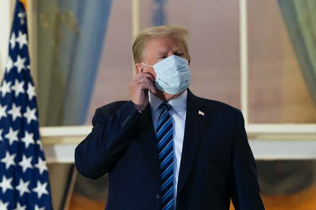 President Donald Trump removes his mask.