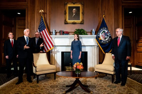 Coney Barrett stands in a stately White House room with Mike Pence and Mitch McConnell, under a portrait of George Washington