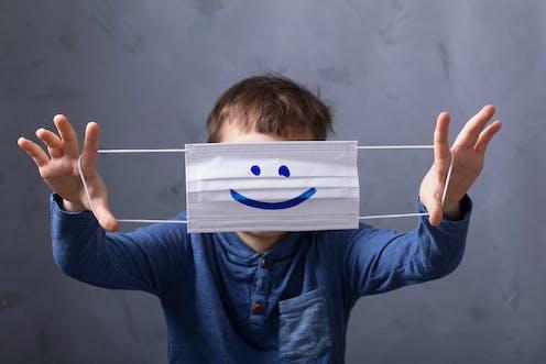 Un niño se tapa la cara mostrando una mascarilla con una sonrisa dibujada.