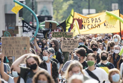 Large group of people marching, while holding signs and wearing masks