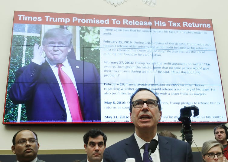 Treasury Secretary Steven Mnuchin testifies during a House Financial Services Committee on May 22, 2019. A screen behind him displays President Trump and a list of times he has promised to release his tax returns.