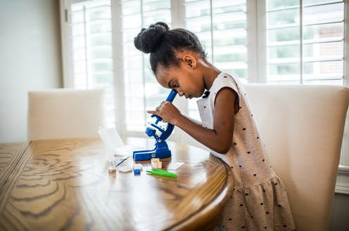 Young girl looks into blue microscope on table.
