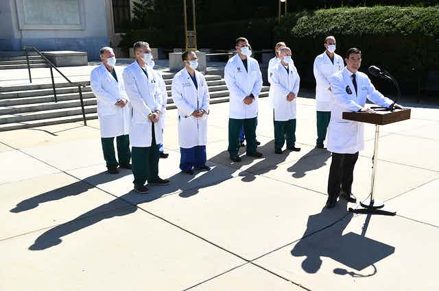 Physicians in white coats give a press conference