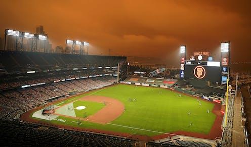 baseball field with reddish hazy sky caused by wildfire smoke.