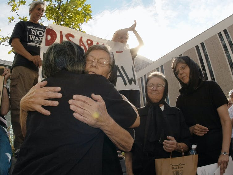 Sister Ardeth Platte, wearing black to honor the international Women in Black movement, being hugged by a supporter ahead of being sentenced in 2003