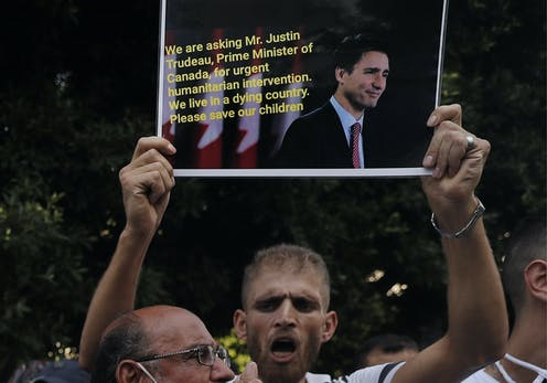 A man holds up a sign pleading for help from Justin Trudeau.