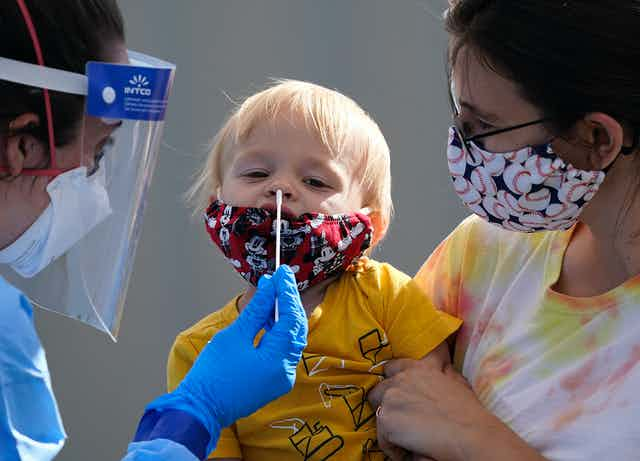 A health-care worker in PPE is about to insert a long swab into a little blond boy's nose as his mother holds him. The boy and his mother are wearing cloth masks.