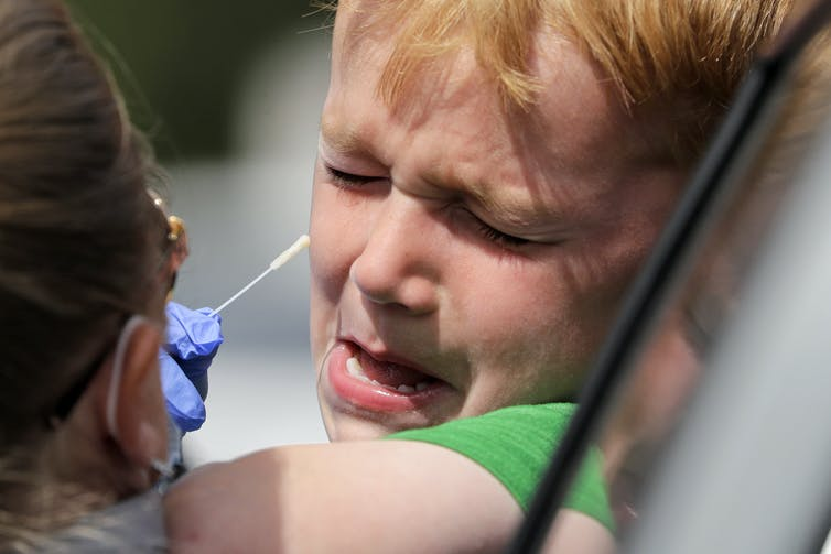 A child sticks his head out a car window and winces as a health-care worker is about to insert a swab in his nose.