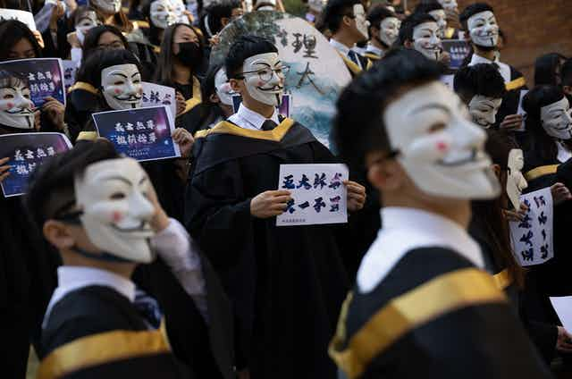 Crowd of students in graduation robes wearing Guy Fawkes masks, holding signs.