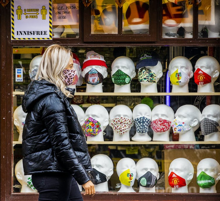 A woman wearing a mask walks past a shop window containing many mannequin heads wearing masks.