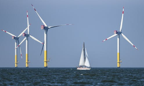Four offshore wind turbines stand amid the North Sea with a white sail boat in the foreground.