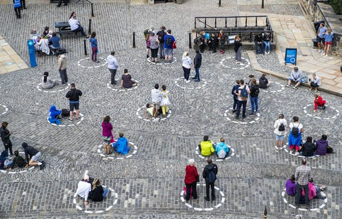 Visitors to Edinburgh socially distance in circles painted on the ground.