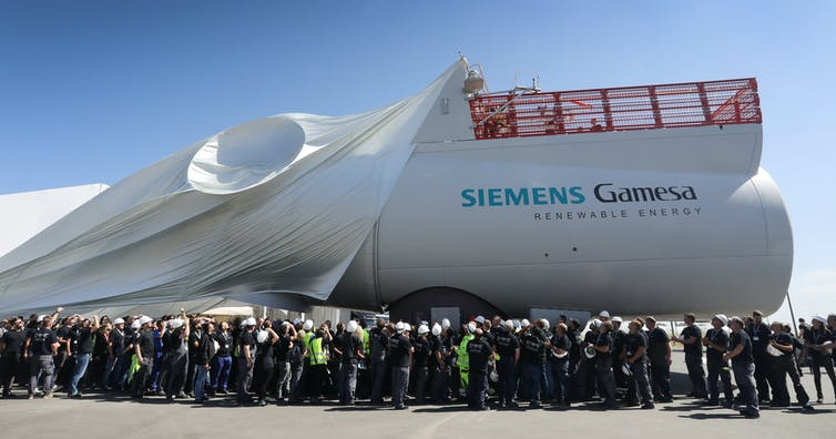 Workers unveil a massive white wind turbine engine.