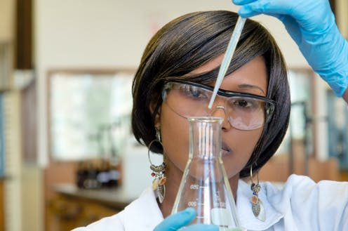 Woman scientist in lab adding drops with pipette to flask