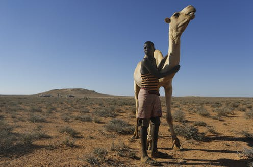 Young man poses with camel in desert scrub landscape.