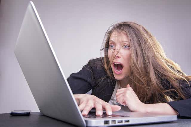 Woman with messed up looks in horror at computer screen.