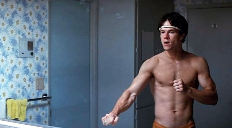 Dirk Diggler, played by Mark Wahlberg, poses in front of a mirror shirtless.