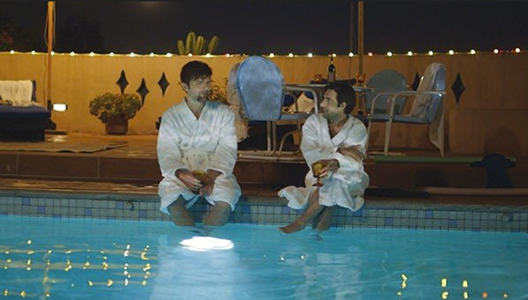 Actors Adam Scott and Jason Schwartzman lounge by the pool in bathrobes in a scene from 'The Overnight.'