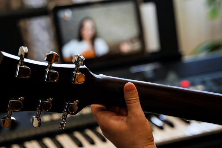 Arm of person playing guitar, with another person playing on screen in background.