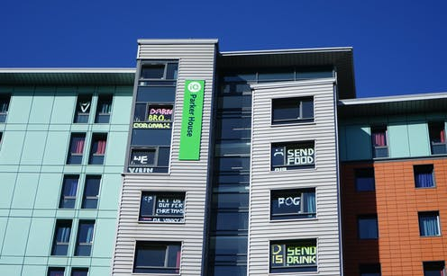 Halls of residence at Dundee University in lockdown with messages on windows saying things like 'Send food and drink'.