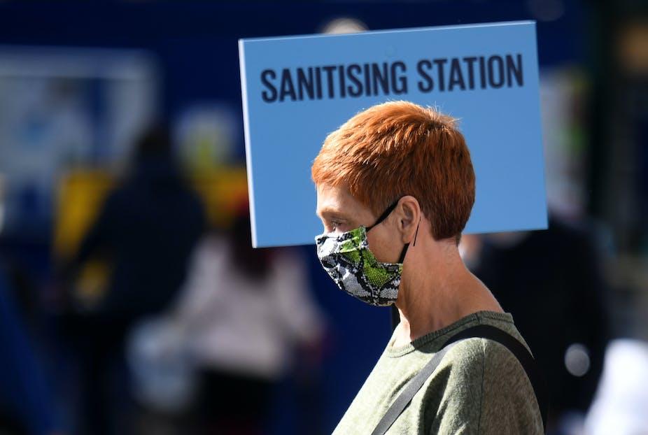 Woman in London walking past sanitising station