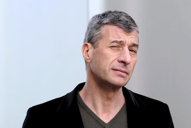Maurizio Cattelan winking in black blazer.