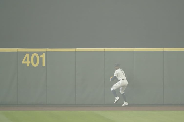 Kyle Lewis prepares to throw the ball back to the infield after making a catch as the air is filled with wildfire smoke during the first baseball game of a doubleheader against the Oakland Athletics, Monday, Sept. 14, 2020, in Seattle.