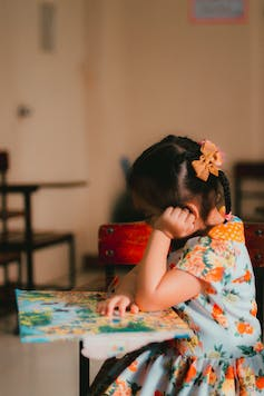 A girl with a bow in her hair sits at a school desk looking at a map.