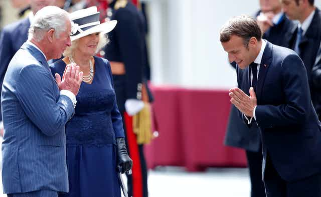 Prince Charles and Emmanuel Macron greet each other with prayer hands