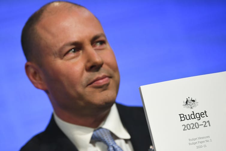 Treasurer Josh Frydenberg holds the 2020-21 budget papers