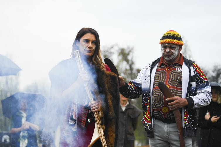 Woman and man stand alongside smoking fire in Indigenous colours.