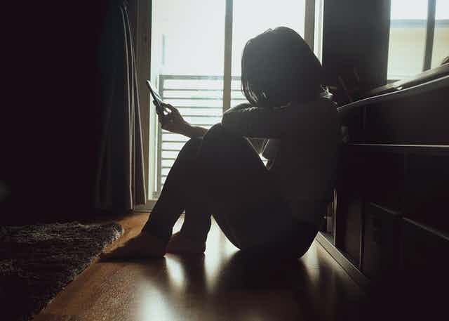 A person sitting on the floor looking at phone, sad and distressed